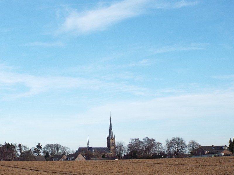 Bolle akker met in de verte de kerk van Liessel