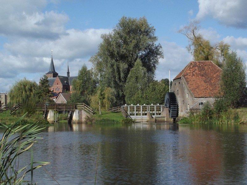 Watermolen de Friedesse Molen met in de verte de kerk van Neer